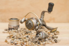 Attira senza titolo, ciottoli, sui precedenti di legno con la bobina merci per pescare 11 05 2016 Fotografia Stock