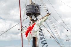 Attirail d'un vieux navire de navigation - un m?t, un m?t, a soulev? les voiles blanc rouge, cordes image libre de droits