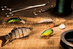 Attirails de pêche, amorce artificielle sur un prédateur sur un fond en bois, wobblers de vue supérieure et diverses cordes et pi Image libre de droits