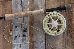 Attirails et attirail de pêche de mouche sur le bois superficiel par les agents image stock