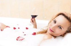 Attirant la détente femelle blonde sexy et sensuelle à Bath mousseux couvert de Rose Petals Vin rouge potable photo stock