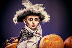 Attire boy. Little boy in halloween costume of pirate posing with pumpkins over dark background Royalty Free Stock Photo