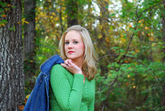 Attitude. A young lady dressed in a green sweater holding a denim jacket.  She has attitude and is in an outdoor setting Royalty Free Stock Photography
