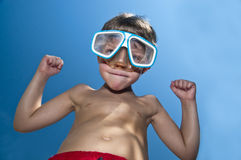 Attitude. Young boy with attitude showing his muscles and wearig swiming googles royalty free stock photo