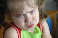 Attitude Adjustment. Little girl struggles with her attitude. Her lips are pooched out and her brow is furrowed. Closeup image royalty free stock photo