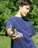 Attitude boy and phone. Boy with attitude holding out cell phone,focus on cell phone stock photos