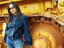 Attitude Dame. A beautiful damsel with an attitude posing in front of a heavy machinery background Stock Photography