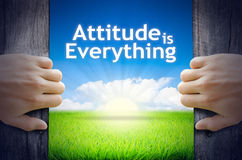 Attitude is everything. Motivational quotes Attitude is Everything . Hands opening a wooden door then found a texts floating among new world as green grass field Stock Photo