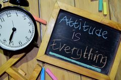 Attitude is Everything on phrase colorful handwritten on chalkboard. And alarm clock with motivation, inspiration and education concepts. Table background royalty free stock image