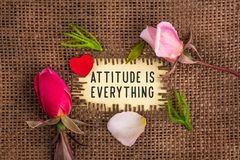 Attitude is everything written in hole on the burlap. With rose flowers and wooden red heart stock photo