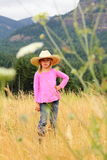 Attitude in the field. A little 6 year old girl with blond hair wearing a cowboy hat and an attitude, standing in tall grass with mountains in the background Royalty Free Stock Photography