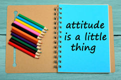 Attitude is a little thing. Text on notebook stock photos