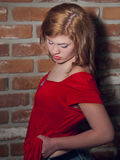 Attitude in a Red Shirt. Beautiful young redhead in a red shirt against a brick wall Stock Photo