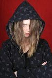 Attitude teen. Troubled teenager with hooded sweater on a red background showing attitude stock photo