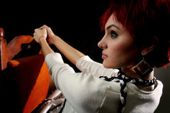 Attitude of a young woman. With red hair in soft light on black background stock images