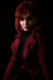 Attitude of a young woman. Young woman with red hair in soft light on black background royalty free stock photography