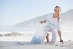 Attivista biondo che prende rifiuti sulla spiaggia fotografie stock