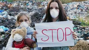 Attivisti della famiglia con il manifesto di arresto sullo scarico residuo stock footage