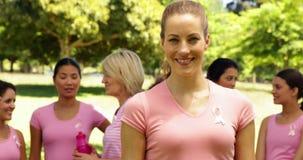 Attivisti per consapevolezza del cancro al seno nel parco uno che sorridono alla macchina fotografica archivi video