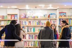 Attività della gente sui libri di acquisto in biblioteca Immagine Stock Libera da Diritti