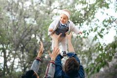 Attività felice di aria aperta della famiglia, bambino di aumenti del padre su, ridendo e giocando, madre di manifestazioni del p fotografia stock libera da diritti