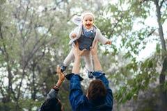 Attività felice di aria aperta della famiglia, bambino di aumenti del padre su, ridendo e giocando, madre di manifestazioni del p fotografie stock libere da diritti
