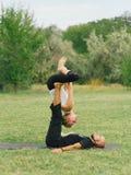 Attività moderna di stile di vita sano Giovani coppie che fanno posa di yoga dell'uccello di acro Fotografie Stock
