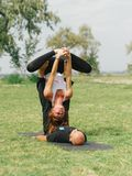 Attività moderna di stile di vita sano Giovani coppie che fanno posa di yoga dell'uccello di acro Fotografia Stock