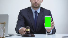 Attorney banging gavel holding cellphone, constitutional law in mobile apps. Stock footage stock video footage