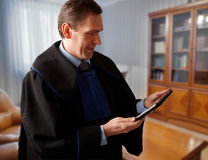 Attorney with tablet. Attorney wearing classic gown with tablet in his office royalty free stock photos