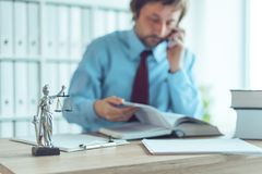 Attorney talking on mobile device. In law office, selective focus on statue of Lady Justice royalty free stock photos