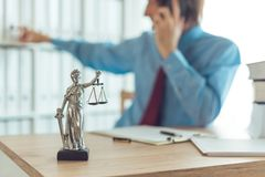Attorney talking on mobile device. In law office, selective focus on statue of Lady Justice royalty free stock photography