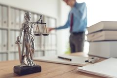 Attorney talking on mobile device. In law office, selective focus on statue of Lady Justice royalty free stock images