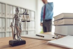 Attorney talking on mobile device. In law office, selective focus on statue of Lady Justice stock photo