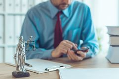 Attorney texting on mobile device. In law office, selective focus on statue of Lady Justice stock photos