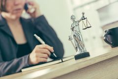 Attorney woman talking on mobile phone from her office desk. Selective focus stock photos