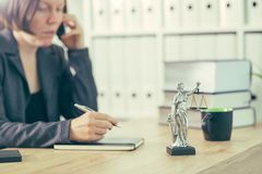 Attorney woman talking on mobile phone from her office desk. Selective focus stock image