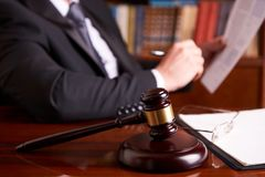 Attorney working, holding Law document. With judge`s gavel at desk in courtroom lawyer office, tribunal and justice concept Stock Images