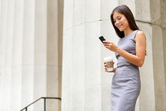 Attorney - young asian woman lawyer. Looking at mobile smartphone and drinking coffee from disposable paper cup. Young multiethnic female professional in the royalty free stock photo