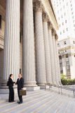 Attorneys Shaking Hands On Courthouse Steps. Full length side view of male and female attorneys shaking hands on courthouse steps Royalty Free Stock Image
