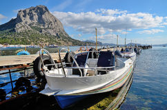 Attracco della barca e un'alta montagna sulla baia sul Mar Nero in Crimea, Novy Svet Fotografia Stock