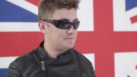 Attracitve-Mann mit modernem Haarschnitt und Sonnenbrille in der Motorradjacke singt stock video footage