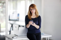 Attracitve professional woman checking emails on her cellphone Royalty Free Stock Photos