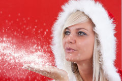Attracive girl in santa cloth. Blowing snow from hands Stock Photo