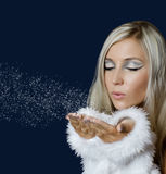 Attracive girl in santa cloth blowing snow. From hands on blue background Stock Images