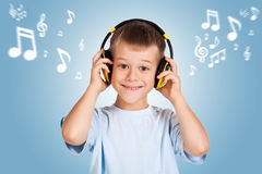 Attracive kid is listening music with headphones Stock Photography