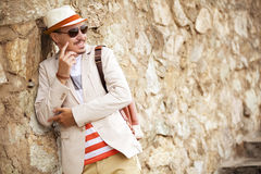 Attracive serious fashion man posing near wall. summer photo. Cool fashion man in hat and glasses with bag, standing by wall Stock Photo