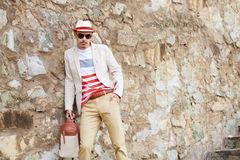 Attracive serious fashion man posing near wall. summer photo. Cool fashion man in hat and glasses with bag, standing by wall Royalty Free Stock Images
