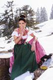 Attract attention with the perfect Dirndl. Very beautiful woman in a fashionable Dirndl sitting on a tree stump in the spring, surrounded by snowfields and stock photos
