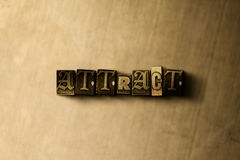 ATTRACT - close-up of grungy vintage typeset word on metal backdrop Stock Photos
